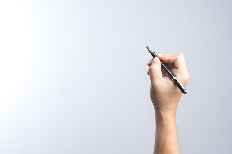 Hand holding a pen for signing or writing